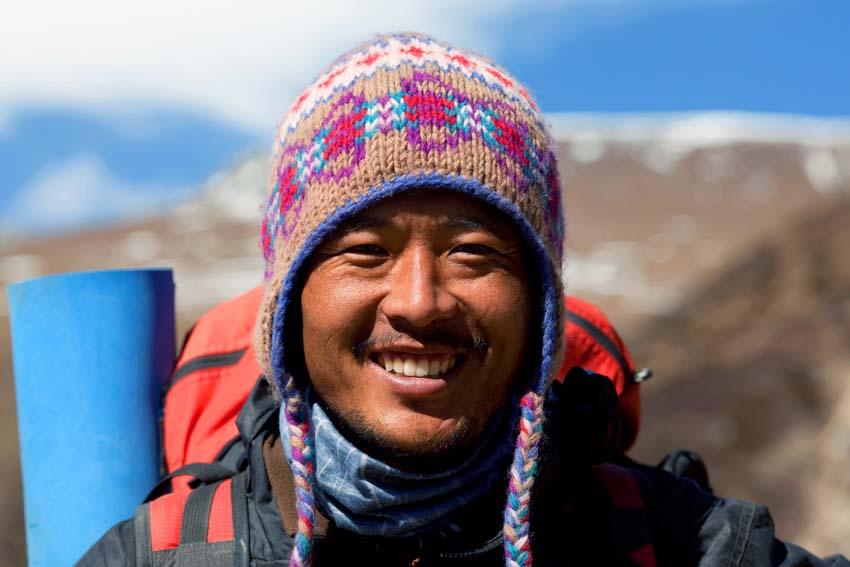 Larke Pass, Manaslu Conservation Area, Nepal - December 01, 2009: Smiling trekking guide poses for a photo on the pass in the Nepal Himalaya.